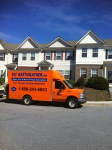 water-damage-restoration-truck-at-flooded-townhouse